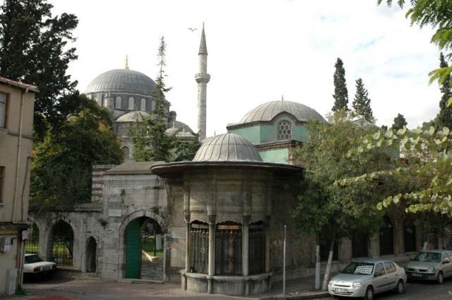 """Yine Fatih'te Hekimoğlu Ali Paşa Camii'ne uğrarsanız zarif sebili ve geniş bahçesi ile sizi karşılar. İsterseniz hamuşanın şahideleri arasında dolaşır, isterseniz Tarihi Uygulamalı Türk İslam Sanatları Kütüphanesi'nden yayılan musikiye kulak verirsiniz. Orada bulunduğum sırada """"Huzur romanının İstanbul'u"""" gezileri yapan grupla karşılaşmam hoş bir tesadüftü. Siz de bu eser veya farklı eserlerden İstanbul rotalarının peşine düşebilirsiniz."""